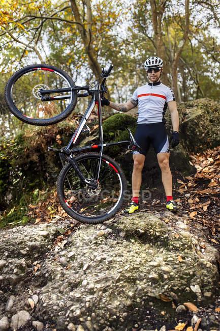 Mountain bike con la sua bici nel bosco — Foto stock