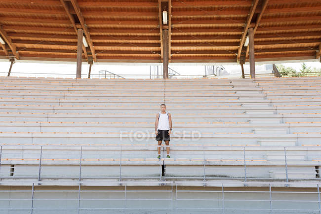 Young sportsman standing on tribune — Stock Photo
