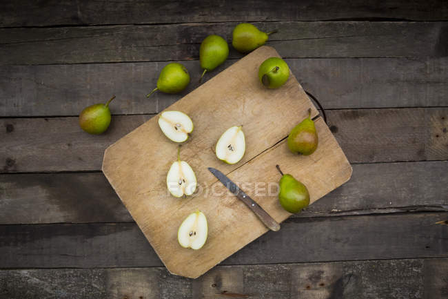 Whole and sliced pears with kitchen knife on wooden board — Stock Photo