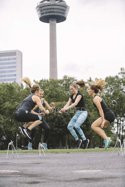 Four women jumping during outdoor workout — Stock Photo