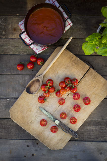 Slices and whole tomatoes on chopping board and cooking pot of tomato soup — Stock Photo