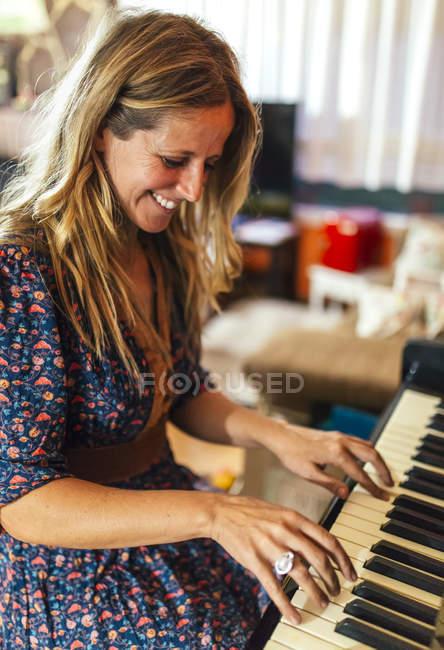 Sonriente mujer tocando el piano - foto de stock