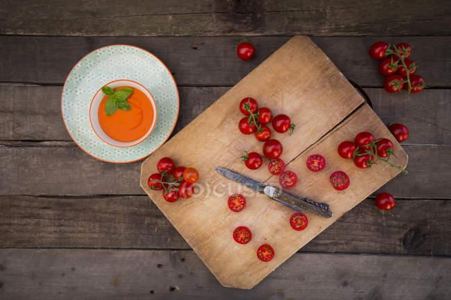 Bol de crème de tomate soupe et hacher planche avec les tomates entières et tranchées — Photo de stock