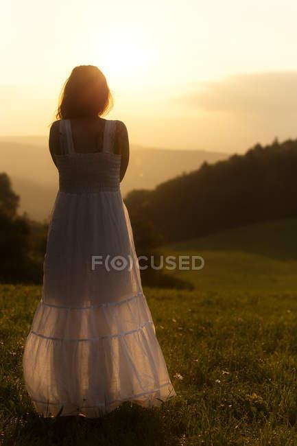 Visão traseira da mulher no prado alpino assistindo nascer do sol — Fotografia de Stock