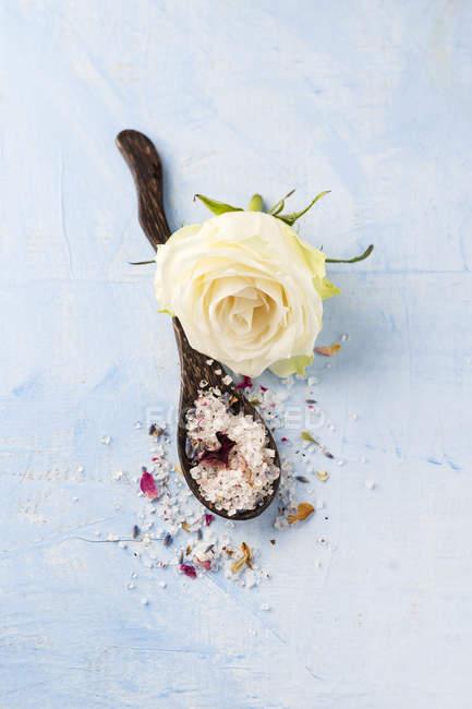 Flor de rosa branca e colher de madeira de sal de banho de lavanda rosa — Fotografia de Stock