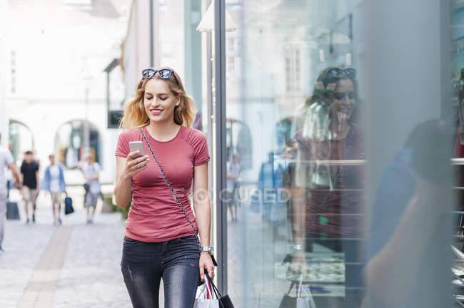 Улыбающаяся женщина идет по улице с сумками, глядя на свой смартфон — стоковое фото