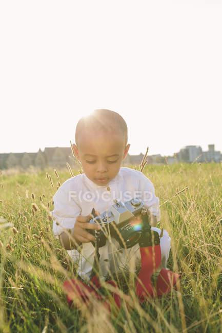 Мальчик сидит в поле и смотрит в камеру — стоковое фото