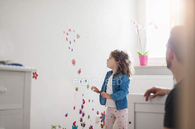 Girl looking at decorated wall in children's room — Stock Photo