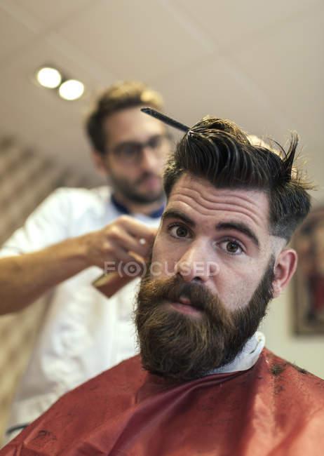 Retrato de homem barbudo em uma loja de barbeiro — Fotografia de Stock