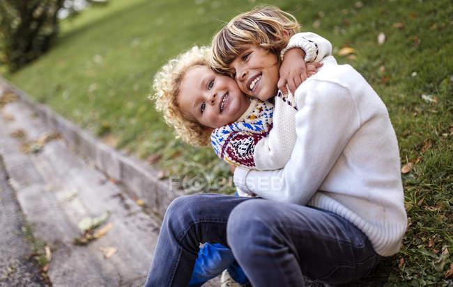 Dos hermanos rubios jugando juntos en otoño - foto de stock