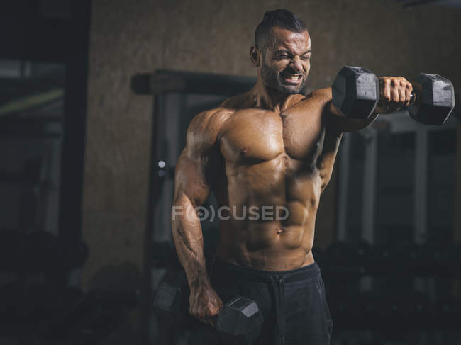 Bodybuilder exercising with dumbbells in gym — Stock Photo