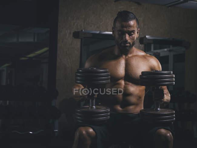 Bodybuilder reposant avec haltères lourdes sur les genoux dans la salle de gym — Photo de stock