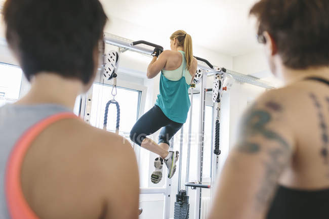 Two women watching athlete doing pull-ups in gym — Stock Photo