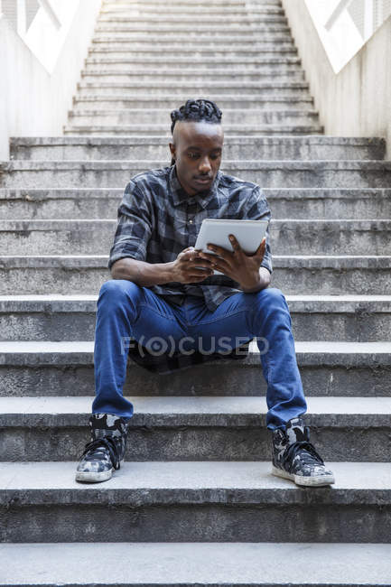 Young man sitting on stairs, using digital tablet — Stock Photo