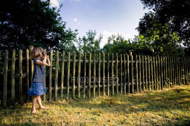 Девушка стоит на лугу и смотрит что-то с биноклем — стоковое фото