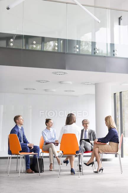 Бизнесмены, сидя в кругу говорить — стоковое фото