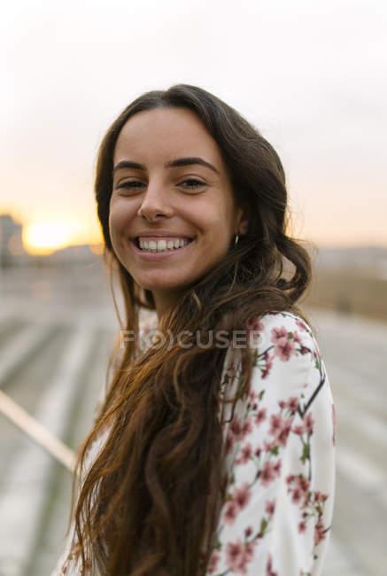 Porträt einer lächelnden Frau in der Abenddämmerung — Stockfoto