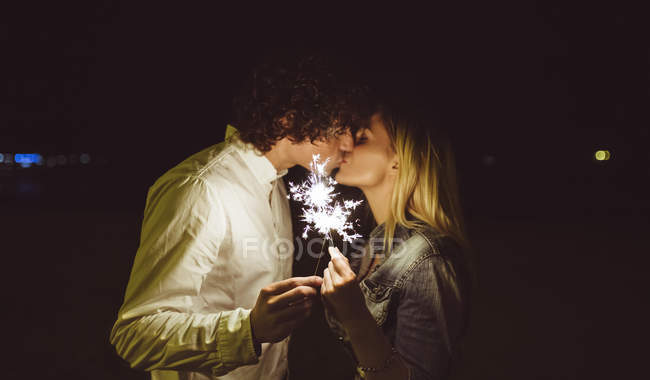Kissing young couple holding sparklers on the beach at night — Stock Photo