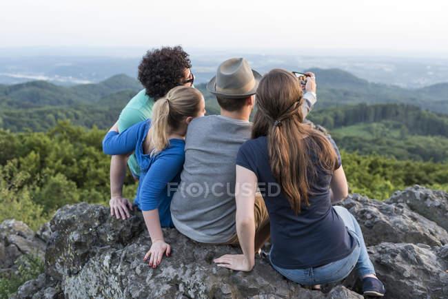 Alemania, Siebengebirge, cuatro amigos tomando selfie con smartphone en Mount Olivet - foto de stock