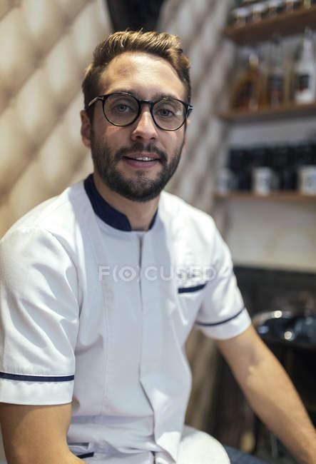 Портрет Барбер з бородою і окуляри, дивлячись в камеру в перукарні — стокове фото