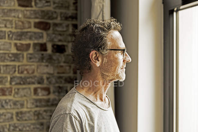 Mature man in spectacles looking through window, side view — Stock Photo