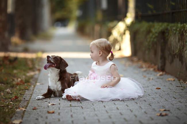 Petite fille blonde portant une robe en tulle assise à côté de son chien sur le trottoir — Photo de stock