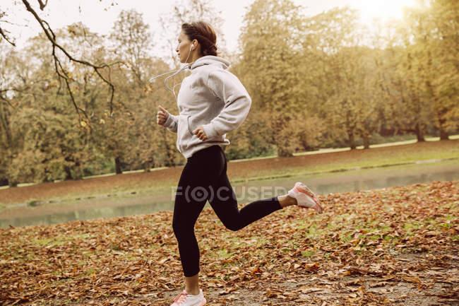 Femme jogging dans le parc pendant l'automne — Photo de stock