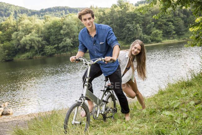 Jovem casal com bicicleta à beira do lago — Fotografia de Stock