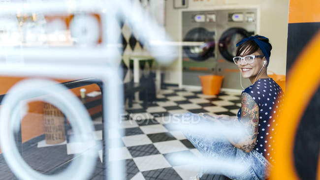 Татуйовані молода жінка слухання музики з навушниками в Пральня — стокове фото
