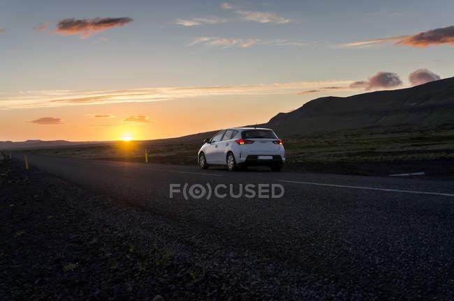 Iceland, car on road under midnight sun — Stock Photo