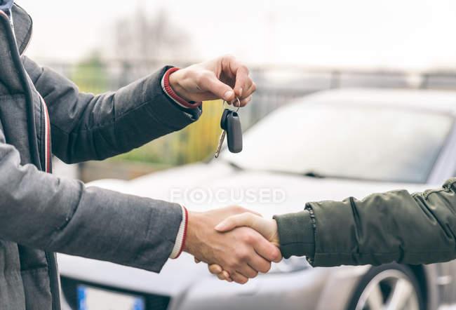 Двоє людей домовлятися про продаж автомобілів — стокове фото