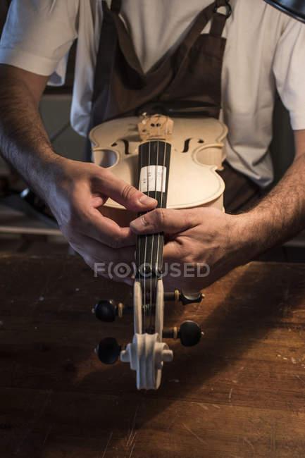 Gitarrenbauer Prüfung eine ungeschminkte Violine in seiner Werkstatt — Stockfoto