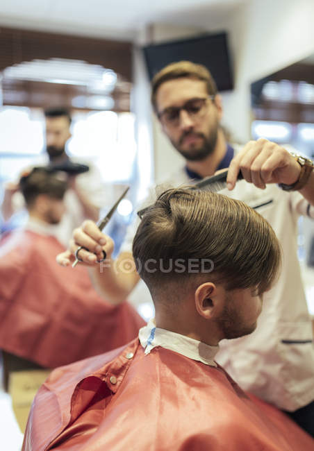 Barbers cutting hair of twin brothers in barber shop — Stock Photo