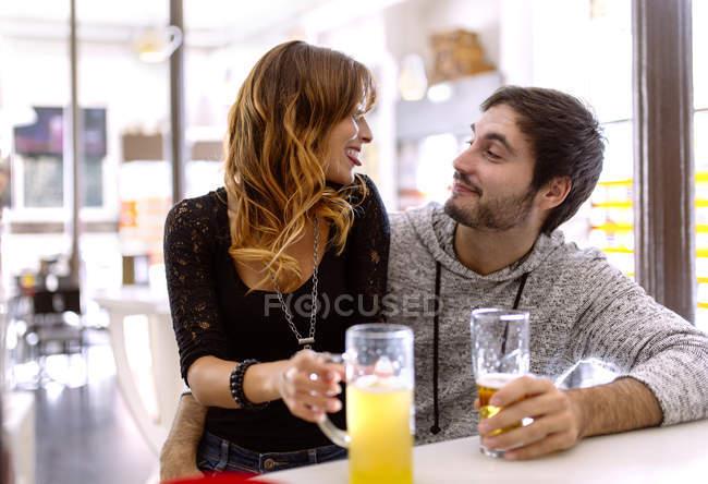 Junges paar entspannende mit Getränken im pub — Stockfoto