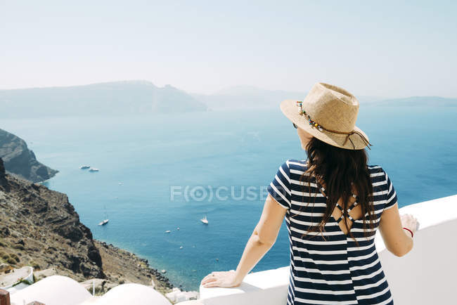 Greece, Santorini, Oia, woman with straw hat looking to the sea — Stock Photo