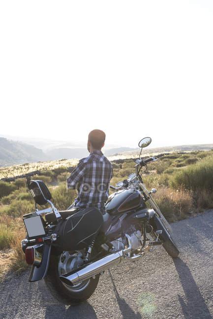 Hombre de pie al lado de la moto en carretera - foto de stock