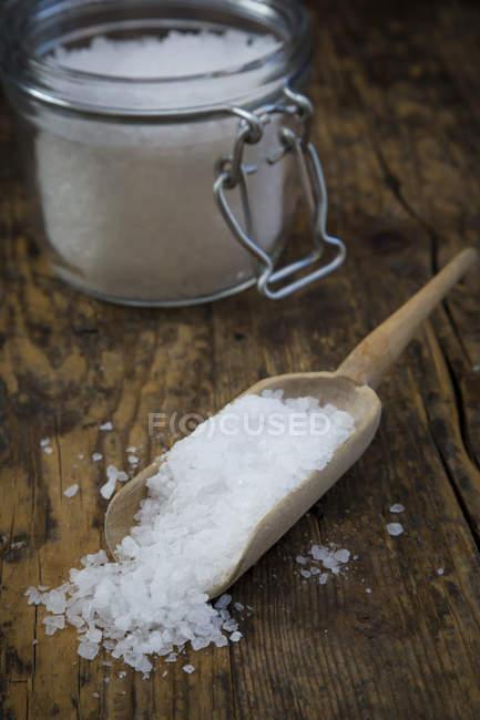 Збереження jar й дерев'яною лопаткою морської солі на темного дерева — стокове фото