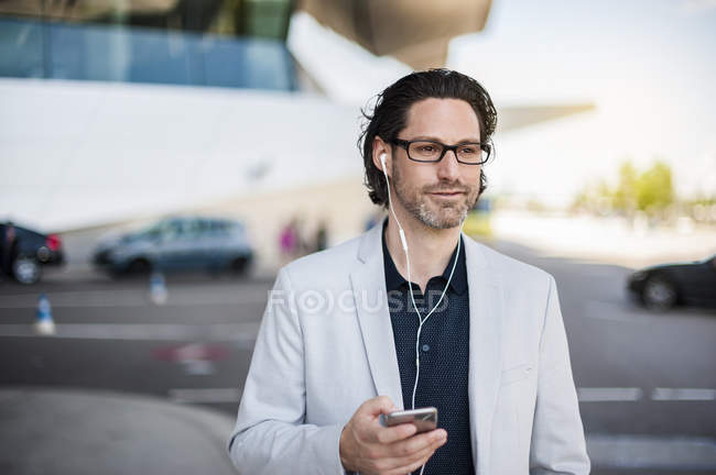 Businessman using smartphone with earphones — Stock Photo