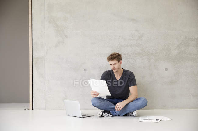 Young man sitting on floor reading documents — Stock Photo