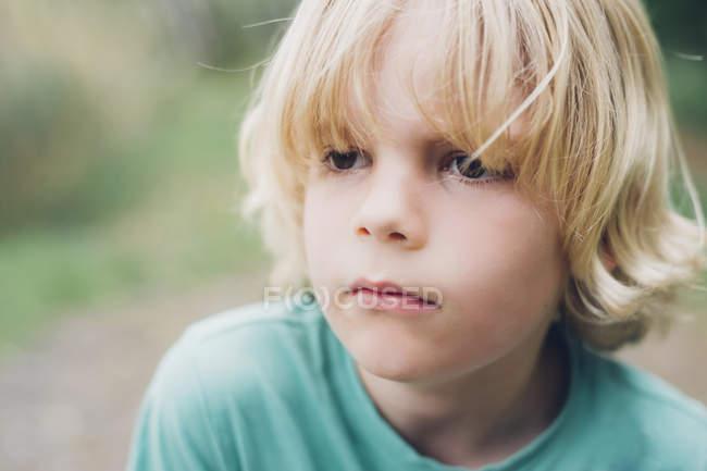 Retrato de un chico rubio serio al aire libre - foto de stock