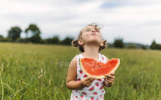 Малыш Девочка держит кусок арбуза с отсутствующих укус — стоковое фото