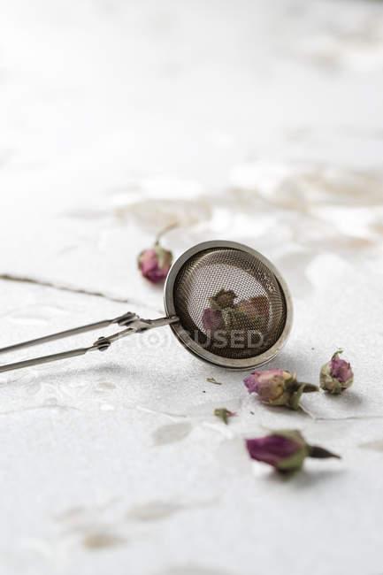 Filtro de chá com pedais de rosa secos — Fotografia de Stock