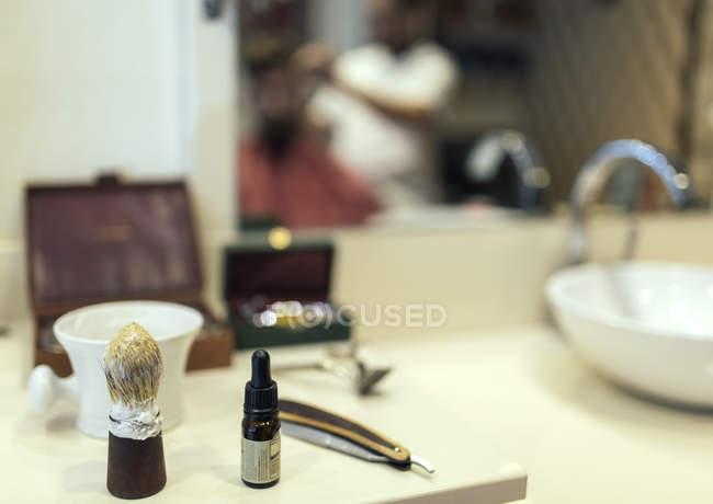 Primo piano degli utensili davanti allo specchio nel negozio di barbiere — Foto stock