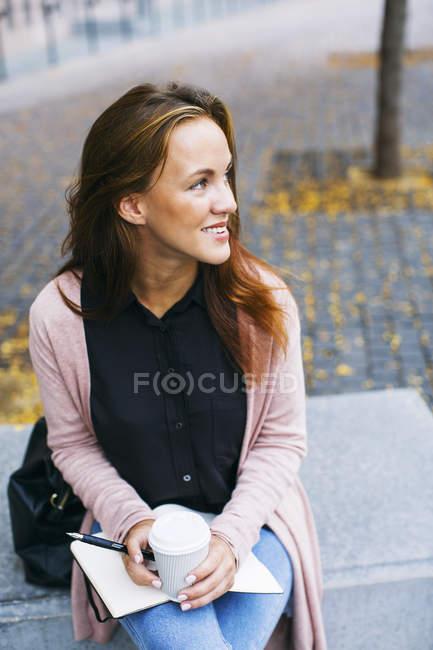 Усміхаючись молода жінка сидить на лавці з ноутбук та каву йти — стокове фото
