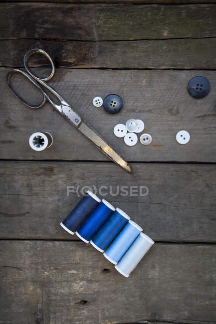 Tijeras con botones y carretes de algodón sobre madera - foto de stock