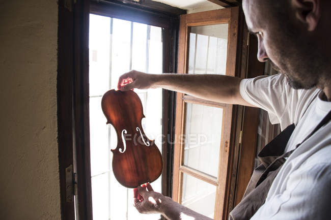 Luthier examining the top plate of a violin in his workshop — Stock Photo