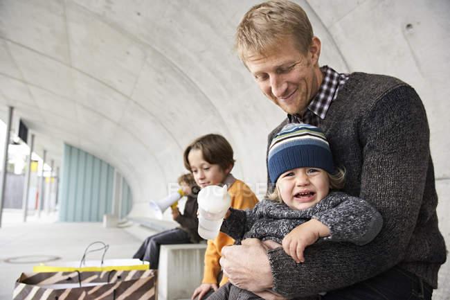 Плачущий мальчик сидит на коленях отца, брат ждет на заднем плане — стоковое фото