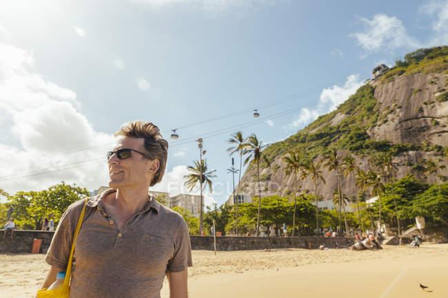 Brazil, Morro da Urca behind a male tourist on Praia Vermelha in Rio de Janeiro — Stock Photo
