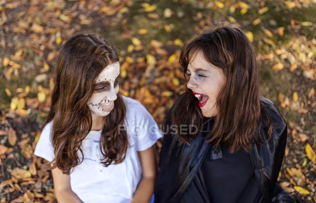 Маленькие девочки в костюмах на Хэллоуин смеются в осеннем парке — стоковое фото