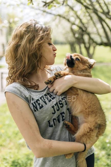 Jeune femme câlinant avec un chiot poméranien — Photo de stock